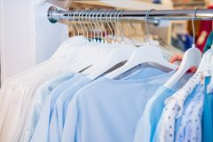 Close up Blue color Clothes on hangers in shop, butique. Make Outfit set. Shopping Mall. Shopper. Sales. Shopping Center. Selectiv. E focus Royalty Free Stock Images