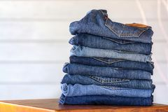 Close up of blue denim jeans. With white background on brown wooden stock photography