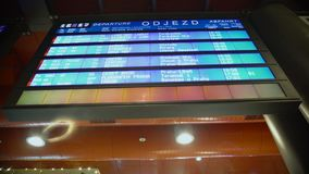 Close-up of blue display screen with train timetables at busy railway station. Stock footage stock footage