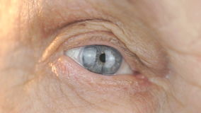 Close-up of blue eye of a woman aged 80s stock video footage