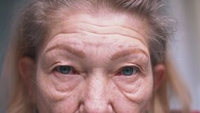 Close up on blue eyes of an elderly woman with wrinkled skin. Depression at old age