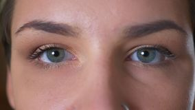 Close-up blue eyes of gorgeous caucasian female looking at camera concentrated and calm.  stock footage