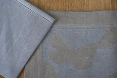 Close-up of Blue and Gray Placemat and Table Napkin Corners. Close-up of blue and gray placemat with embroidered butterfly design and an overlapping matching Royalty Free Stock Images