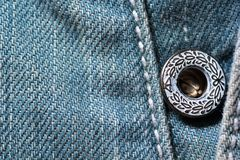 Close up of blue jeans with a lovely decorated button Royalty Free Stock Photo