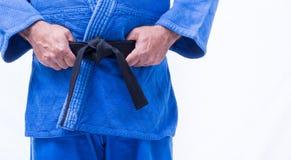 Close up of blue judo uniform, judo-gi, with belt isolated on white Stock Photo
