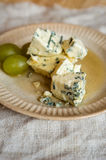 Blue mold cheese and grapes on a plate Stock Images