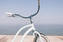 Close-up of a blue retro bicycle against the sea on the beach. Biking on a summer evening Stock Photos