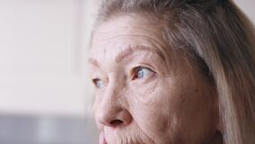 Close up on blue sad eyes of lonely elderly woman looking through the window