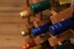 Close up of blue screw top wine bottle with other bottles in a w. Ooden wine rack Stock Photos