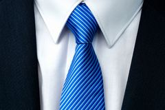Close-up of a blue striped tie. With withe shirt and dark businessman suit royalty free stock photo