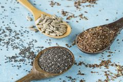 Wooden spoons with sunflower seeds, chia and linseed royalty free stock photo