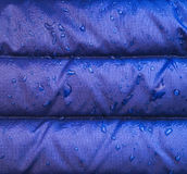 A close up of blue waterproof rain jacket fabric with water droplets. Stock Photos