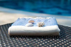 Close-up of blue and white Turkish towel on rattan lounger with blue swimming pool as background. Stock Image