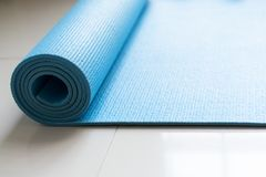 Close up of blue yoga mat on the floor in fitness class royalty free stock images