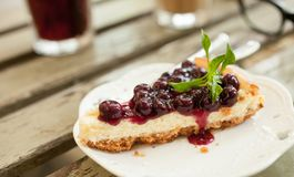 Blueberry cheesecake. Close up blueberry cheesecake slice on the wood table Royalty Free Stock Photography