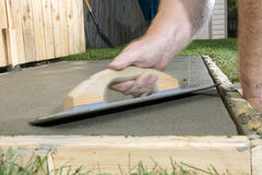 Blurred hand finishing wet cement with screed. A close up of a blurred hand in motion finishing a wet cement slab with a concreting screed in a backyard, DIY Royalty Free Stock Photo
