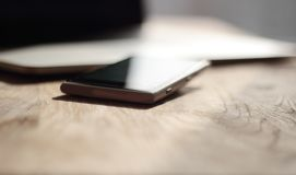 Close up. blurred image of a mobile phone and laptop on the desk stock image