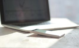 Close up. blurred image of a mobile phone and laptop on the desktop stock photography