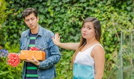 Close up of blurred man holding a gift and flowers with shocked face after see his girlfriend stretching her arm. Close up of blurred men holding a gift and Royalty Free Stock Images