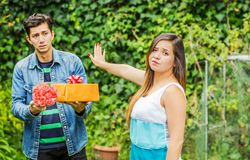 Close up of blurred man holding a gift and flowers with sad face after see his girlfriend stretching her arm ignoring. Close up of blurred men holding a gift and Stock Photos