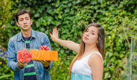Close up of blurred man holding a gift and flowers with shocked face after see his girlfriend stretching her arm. Close up of blurred men holding a gift and Stock Image