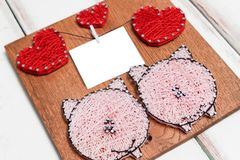 Close - up of the Board with nails wound with threads in the form of hearts and pigs and a piece of paper on a thread.  royalty free stock photo