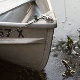 Close-up of boat bow. Close-up of the bow of a moored boat in dirty water Stock Image