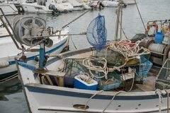 Close up of the boats with fishing gear in the port. Close up of the fishing boats in the port. Mooring of the small fishing vessel at the dock. Fishing gear and royalty free stock image