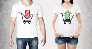 Close up of the bodies of man and woman in a white t-shirts with two sketches: a basket with red arrow and a basket with green arr Stock Image