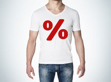 Close up of the body view of the man in a white t-shirt with the red percentage sign on the chest. Concept of the sale. Stock Photo