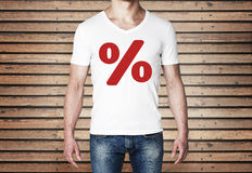 Close up of the body view of the man in a white t-shirt with the red percentage sign on the chest. Stock Images