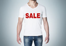 Close up of the body view of the man in a white t-shirt with the red word ' sale ' on the chest. Stock Photos