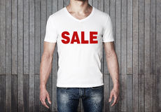 Close up of the body view of the man in a white t-shirt with the red word ' sale ' on the chest. Stock Photography