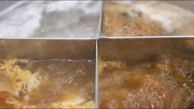 Close up of boiling hot pot contains four sections for different type of soups / broths. Close up of boiling hot pot contains four sections for different types stock video