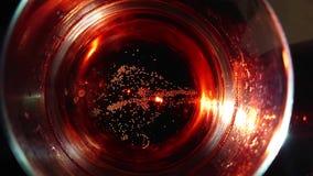 Close-up, bolhas de aumentação no vidro iluminado na parte superior com champanhe vermelho filme