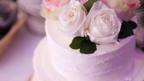 Close-up, bolo de creme neve-branco da três-história, decorado com rosas bolo de casamento tradicional, tradições do casamento video estoque