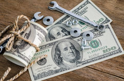Close up bolts nuts and money on wood table. Royalty Free Stock Photography