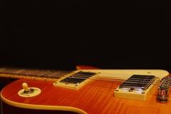 Close up bonde da guitarra dos azuis do vintage do sunburst do mel no fundo preto, com abundância do espaço da cópia imagens de stock royalty free