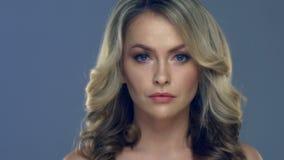 Close-up bonito da cara da jovem mulher no fundo azul vídeos de arquivo