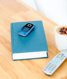 Close-up of book, cellphone, remote, cup of coffee Royalty Free Stock Photography