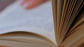 Close-up of book with hands flipping through pages. open book pages. slow motion. Close-up of book with hands flipping through pages stock video footage