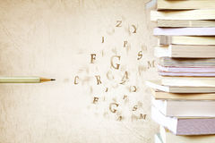 Close up book stacked with the pencil and alphabet letter flyin royalty free stock photography