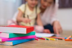 Close up of books on floor with mom and kids background. Back to. School and Education concept. Children and teacher theme royalty free stock photography