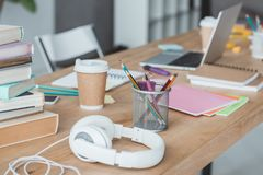 close up of books, headphones, coffee, copybooks and laptop royalty free stock photo
