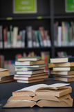Close up of books stack on table against shelf Royalty Free Stock Photo