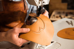 Close up of a bootmaker working with leather textile Royalty Free Stock Photography
