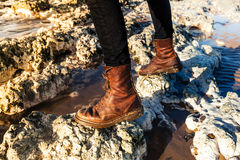 Close up on boots walking among the rocks at beach Royalty Free Stock Image