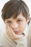 Close-Up Of Bored Boy With Hand On Chin Royalty Free Stock Image