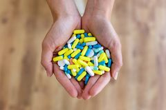 Both hands of young woman holding bunch of pills. Overdose or abuse concept. Close-up of both hands of young woman holding bunch of pills. Overdose or abuse royalty free stock photos