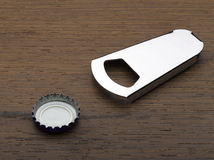 Close up of bottle opener and cap Royalty Free Stock Photo